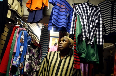 Abdirahman Chirango shows some of the garments in the clothing section of Tork's Cafe. Photo by Mike Christy/Arizona Daily Star.