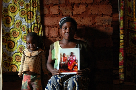 Jackie Niyonzima, 27, and her son Elias Vyizigiro, 5, pose with a picture of her oldest son and her mother who now live in Chattanooga. Money that Jackie's mother sent back to Burundi helped build this small mud house. Perla Trevizo/Chattanooga Times Free Press.