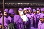 Men, called cucuruchus, dress in purple cloaks, carry a float with the figure of Christ and the cross during the fifth Sunday Lent procession in Antigua, Guatemala. It takes close to 100 men to carry the float that can weigh up to 7,000 pounds. Men generally buy their turn at local church since being a carrier is considered a great honor.