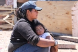 Heidi Sandoval takes a break from sorting plastic and holds her 1-year-old daughter Lizbeth. Heidi lived in a makeshift home by the dump in Nogales, Sonora, but she has now built a home nearby with a help of a U.S. church.