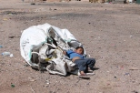 Domingo Sandoval, 4, takes a nap on top of one of the large bags his parents fill with plastic they scavenge from the Nogales, Sonora, dump. In a city where there's no formal recycling program, waste pickers collect plastic, cardboard and aluminum to sell to private companies.